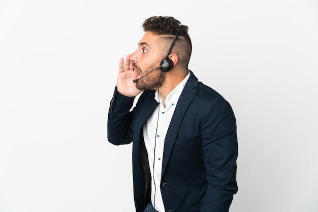 헤드셋으로 작업하는 텔레마케터 남자는 옆으로 입 벌리고 외치는 흰 벽에 고립