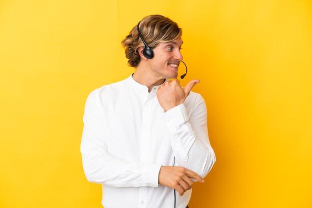 Человек-телемаркетер, работающий с гарнитурой, изолирован на желтом фоне, указывая в сторону, чтобы представить продукт
