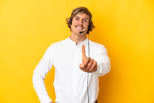 노란색 표시 및 손가락 해제에 고립 된 헤드셋 작업 텔레마케터 남자