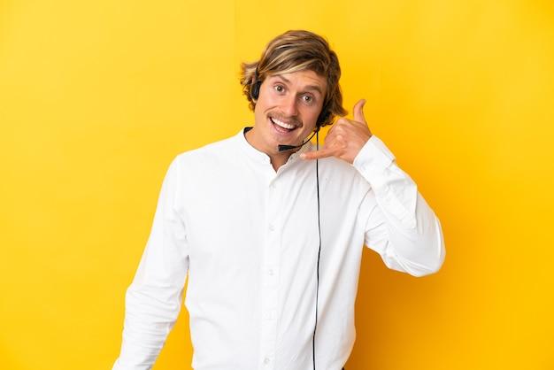 Человек телемаркетинга, работающий с гарнитурой, изолированной на желтой стене, делая телефонный жест. перезвони мне знак