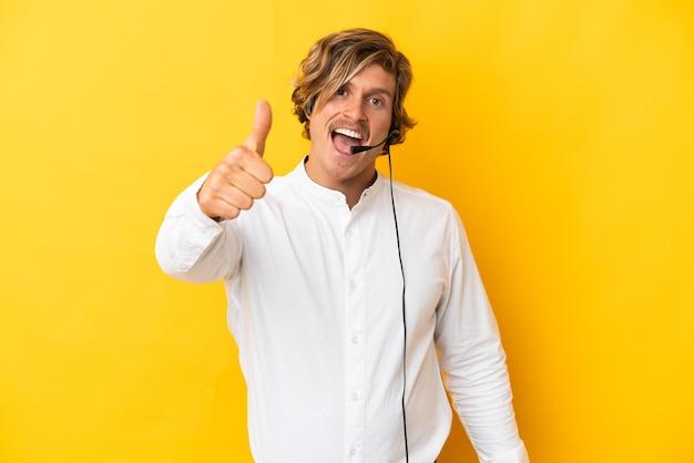 좋은 일이 일어났기 때문에 엄지 손가락으로 노란색 벽에 고립 된 헤드셋으로 작업하는 텔레마케터 남자