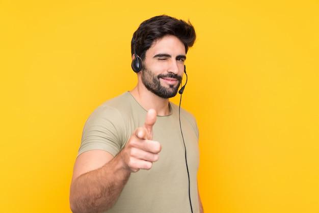 당신에 고립 된 노란색 벽 포인트 손가락 위에 헤드셋을 사용하는 텔레 마케팅 사람
