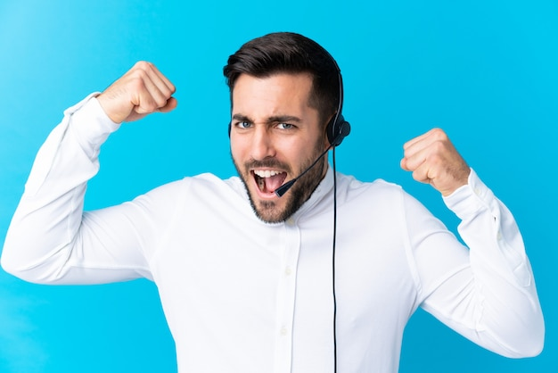 Telemarketer man working with a headset over blue celebrating a victory