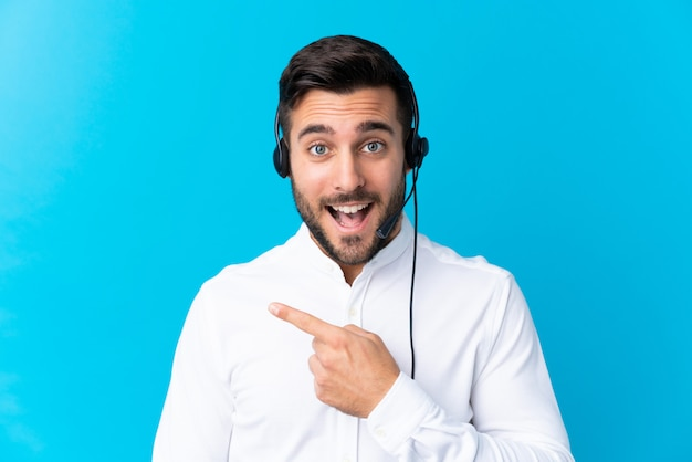 Telemarketer man working with a headset over blue pointing finger to the side