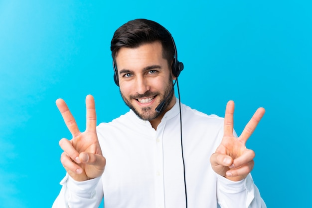 Telemarketer man working with a headset over blue smiling and showing victory sign