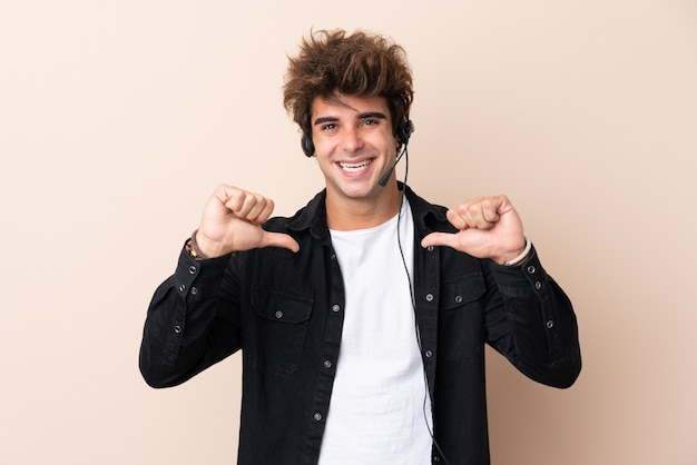 Telemarketer man working with a headset over isolated wall proud and self-satisfied