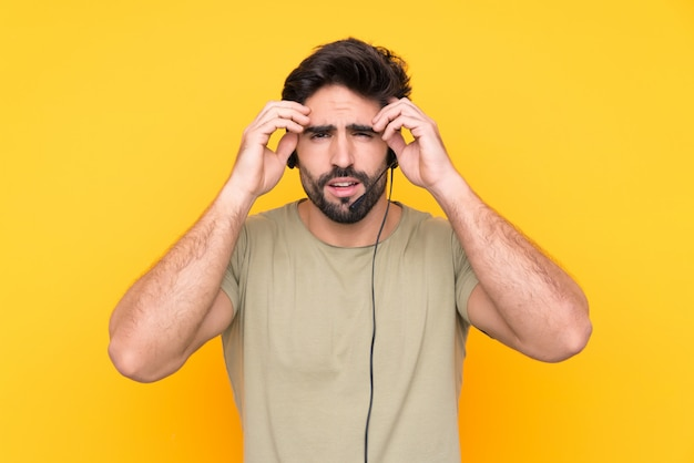 Telemarketer man working with a headset over isolated wall