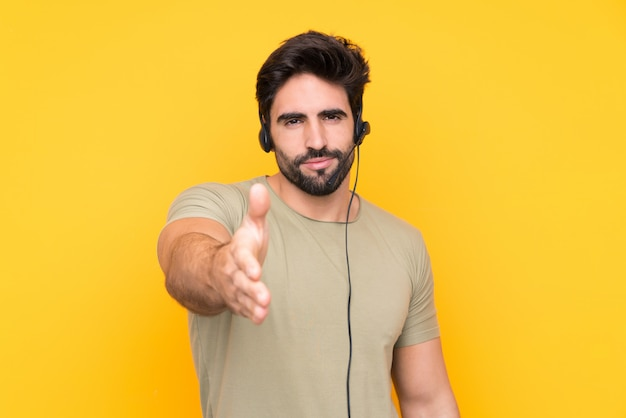 Telemarketer man working with a headset over isolated yellow wall handshaking after good deal