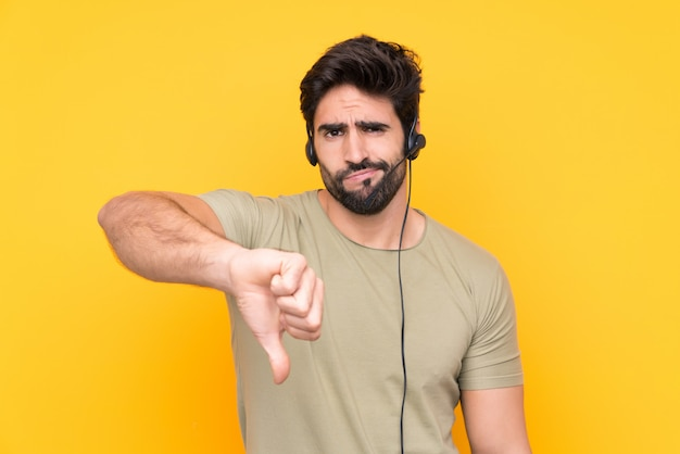 Telemarketer man working with a headset over isolated yellow wall showing thumb down sign