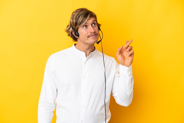 Telemarketer man working with a headset isolated on yellow wall with fingers crossing and wishing the best
