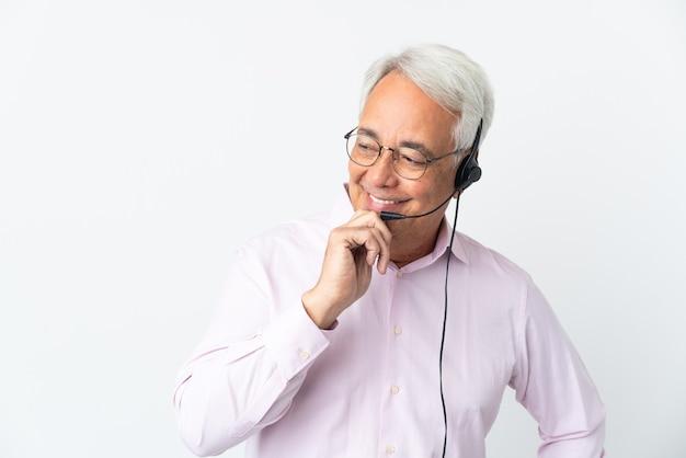 Телемаркетер среднего возраста человек, работающий с гарнитурой, изолированные на белом фоне, глядя в сторону и улыбаясь