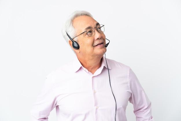 텔레마케터 중년 남자는 흰색 배경에 격리된 헤드셋을 사용하여 찾고 있는 동안 아이디어를 생각하고 있습니다.