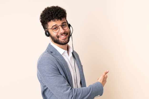 Telemarketer moroccan man working with a headset isolated on beige wall pointing back