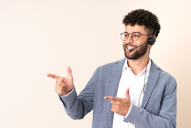 Telemarketer moroccan man working with a headset isolated on beige wall pointing finger to the side and presenting a product