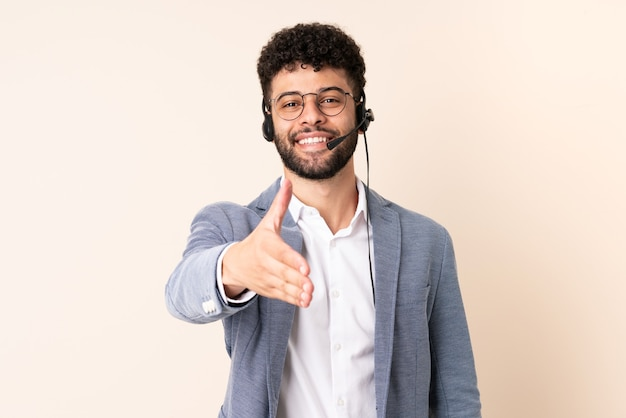 Telemarketer moroccan man working with a headset isolated on beige wall shaking hands for closing a good deal