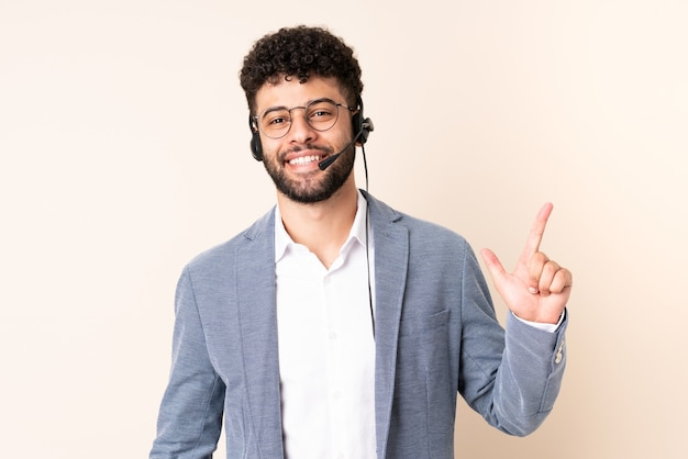 Telemarketer moroccan man working with a headset isolated on beige wall showing and lifting a finger in sign of the best