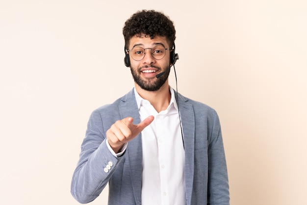 Telemarketer moroccan man working with a headset isolated on beige wall surprised and pointing front