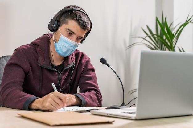 Telemarketer or podcast man working with laptop and talking on a headset with face mask at office