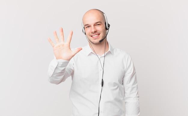 Телемаркетер улыбается и выглядит дружелюбно, показывает пятый или пятый номер рукой вперед, ведет обратный отсчет