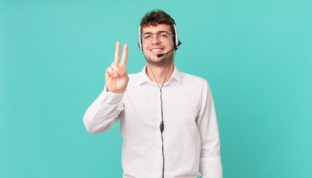 텔레마케터는 웃고 행복하고 근심없고 긍정적이며 한 손으로 승리 또는 평화를 나타냅니다.