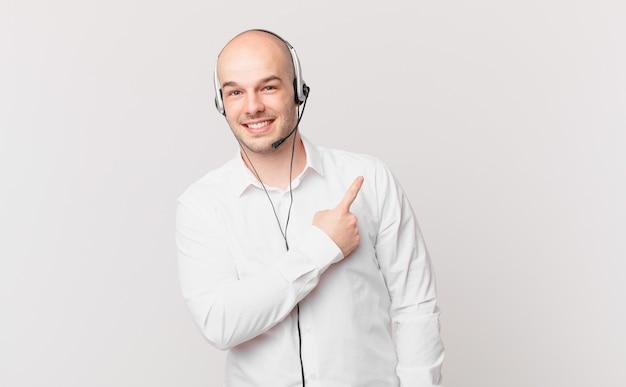 テレマーケティング担当者は、幸せな気分で明るく微笑み、横と上を指して、コピースペースにオブジェクトを表示します