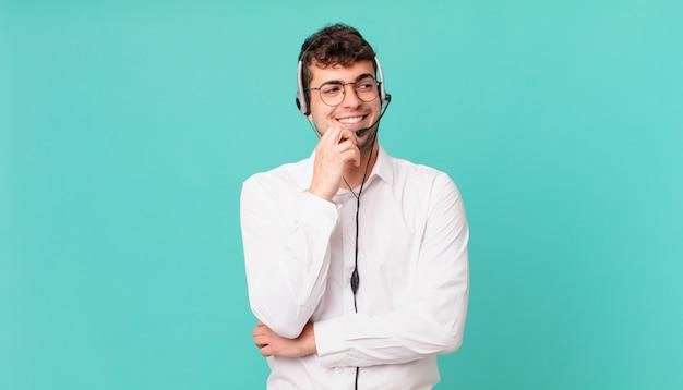 Телемаркетолог улыбается счастливым, уверенным выражением лица, подпирая подбородок, недоумевая и глядя в сторону.