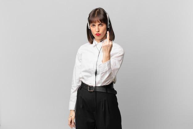 Женщина-телемаркетолог чувствует себя сердитой, раздраженной, мятежной и агрессивной, щелкает средним пальцем, сопротивляется