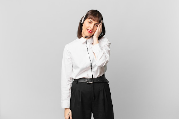 Telemarketer woman feeling bored, frustrated and sleepy after a tiresome, dull and tedious task, holding face with hand