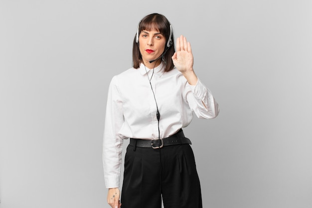 Telemarketer woman looking serious, stern, displeased and angry showing open palm making stop gesture