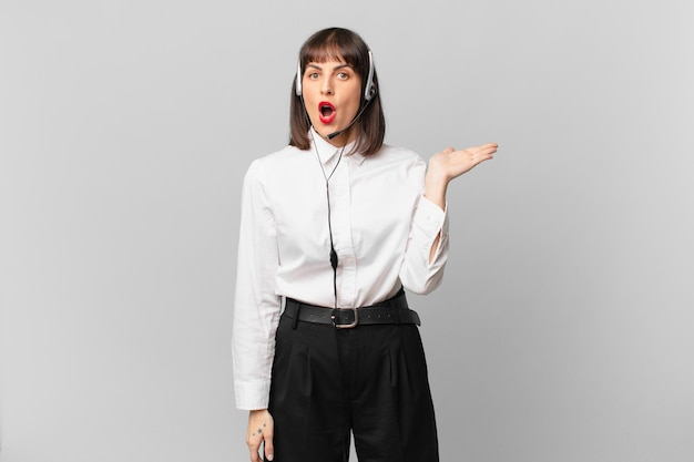 놀라고 충격을 받은 텔레마케터 여성, 옆구리에 열린 손으로 물건을 들고 턱이 떨어졌다