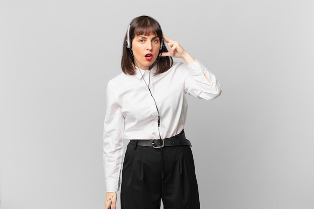 Telemarketer woman looking surprised, open-mouthed, shocked, realizing a new thought, idea or concept