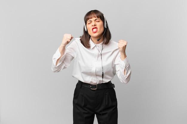 Женщина-телемаркетер, агрессивно кричащая с гневным выражением лица или со сжатыми кулаками, празднует успех