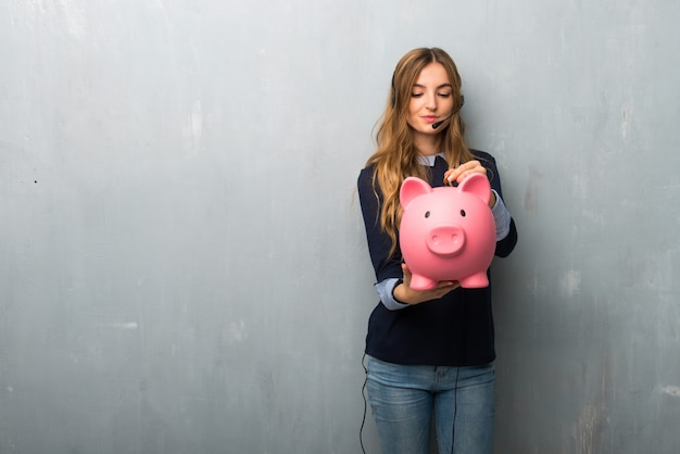 Telemarketer woman taking a piggy bank and happy because it is full