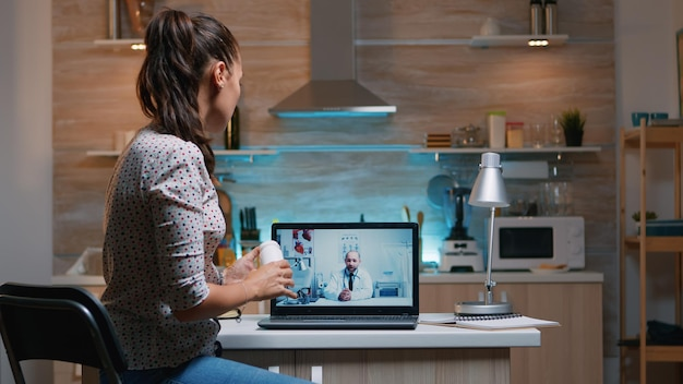 Consultazione di telemedicina durante la pandemia di covid di notte, donna seduta davanti al laptop in cucina. signora malata che discute durante la consultazione virtuale sui sintomi che tengono una bottiglia di pillole