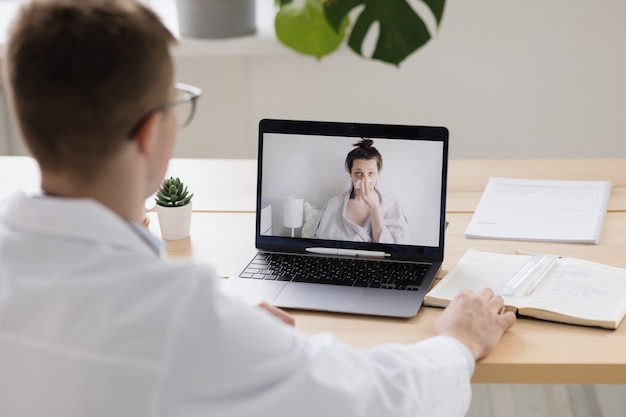 Telemedicine a young adult european and competent doctor in a white coat in a medical clinic in his