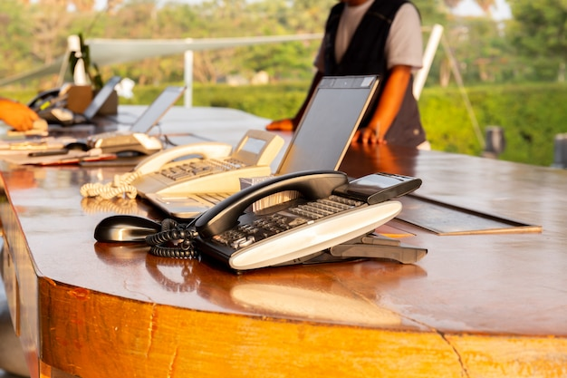 Telephone on hotel reception desk with customer check in at reception counter.