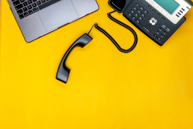 Telephone, laptop flat lay with workspace on yellow background