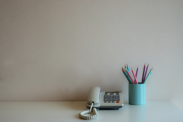 Telephone and pastel pencils in the blue glass on the desk at gray wall background