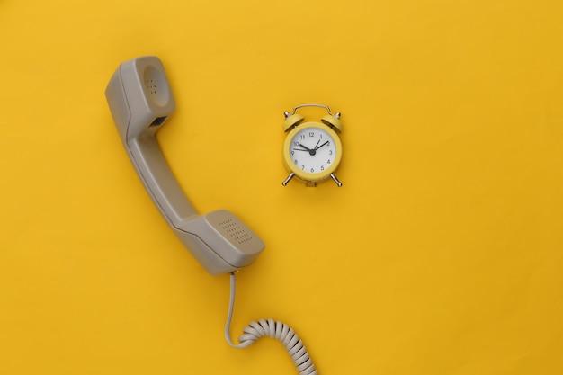 노란색 배경에 전화 수신기와 알람 시계.