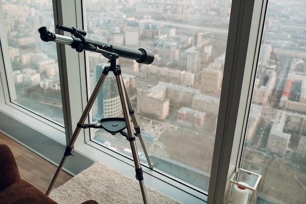 Telescope at window of skyscraper