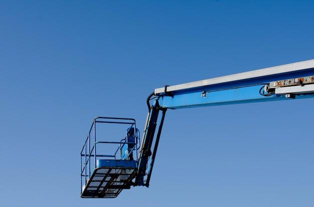 망원경 붐 리프트는 강철 프레임 건설자, 지붕 작업자 및 화가가 사용할 준비가 된 수축 현장으로 전달된 푸른 하늘 배경에 올라갔습니다.