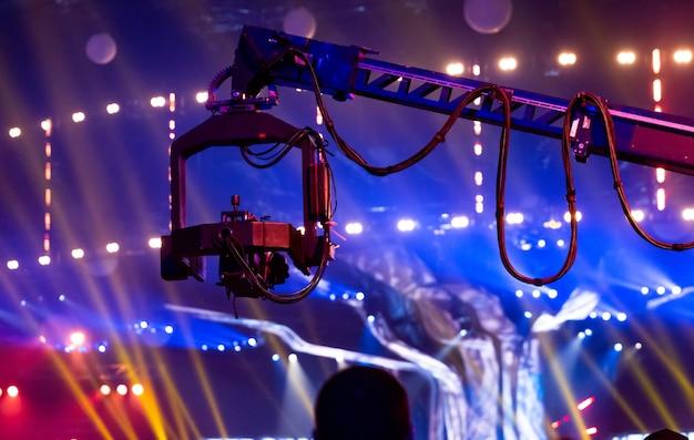 Кран телескопический с прикрепленной видеокамерой. телевидение записывает события. камера со стабилизатором движется над головами публики концерта.