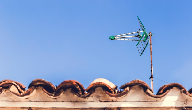 Television antenna on the old roof with blue sky