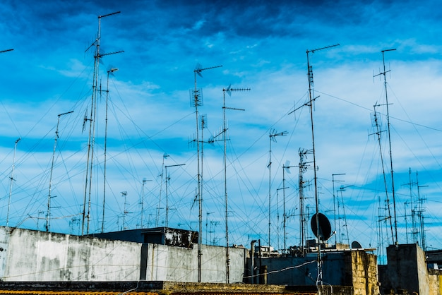 Television antennas on the roof of an old building with dramatic sky.