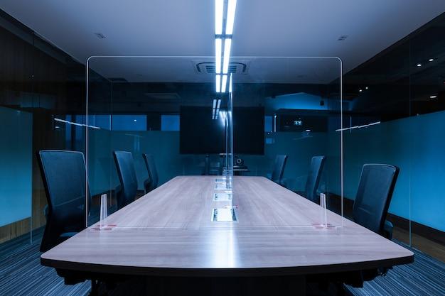 Пустой экран телевизора в зале для видеоконференций с прозрачным акриловым листом отделяет центр конференц-стола от covid-19