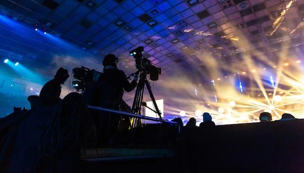 콘서트 중 카메라맨이 방송하는 텔레비전. 오퍼레이터가 있는 카메라는 높은 플랫폼에 있습니다. 다채로운 광선의 배경에 실루엣입니다.