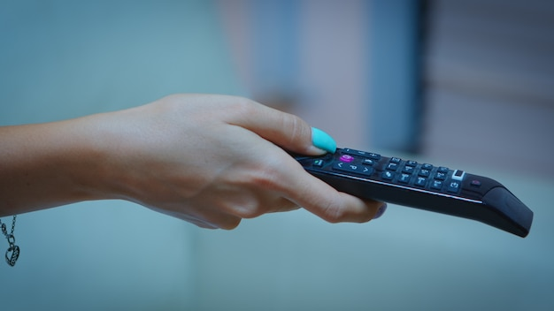 Telecomando televisivo nelle mani della donna che punta alla tv e cambia canale. chiuda in su della donna che tiene il controller e premendo il pulsante seduto sul divano davanti alla televisione. Foto Gratuite