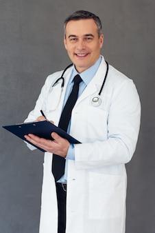 Расскажи мне о своих привычках! зрелый мужчина-врач делает заметки в буфере обмена и смотрит в камеру с улыбкой, стоя на сером фоне