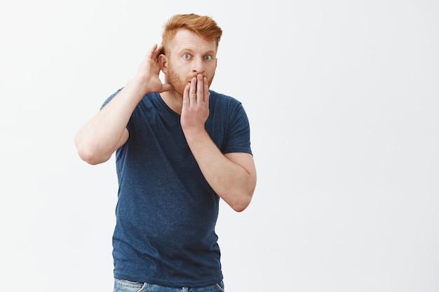 注意深く聞いて、噂の詳細をすべて教えてください。青いtシャツを着た、ショックを受けた印象的なハンサムな赤毛の男、かがむ、驚きの口から開いたカバー、耳の近くで手をつないで、盗聴