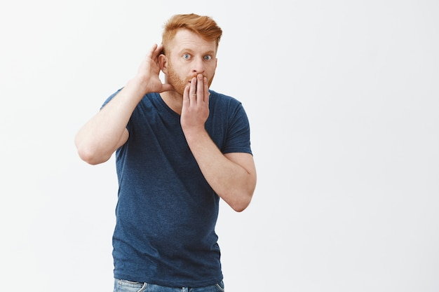 Tell me all details of rumor, listening carefully. shocked impressed handsome redhead guy in blue t-shirt, stooping, covering opened from amazement mouth, holding hand near ear, eavesdropping